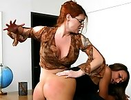 Busty red head with glassess uses her hands to spank cheating girl in class